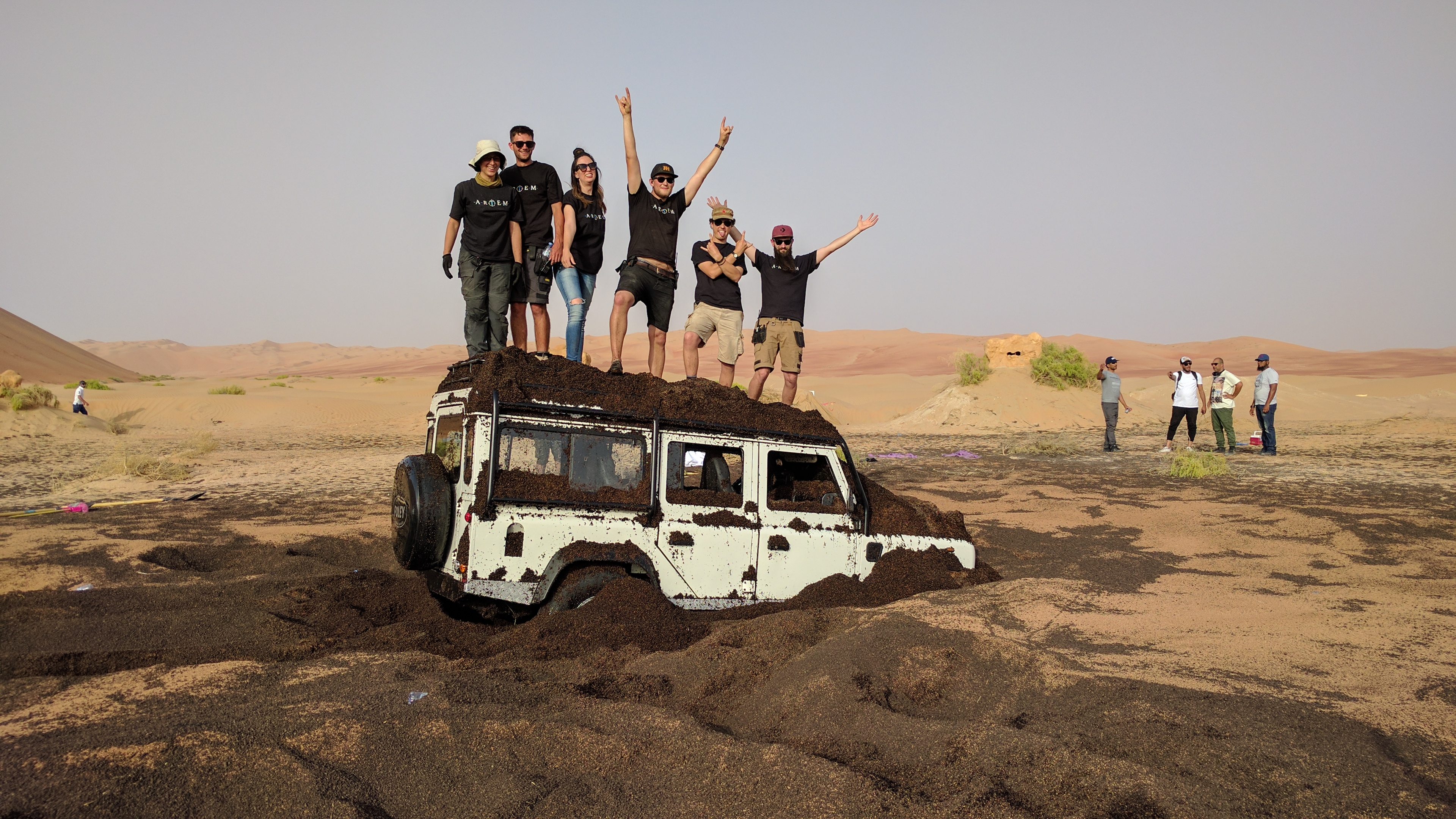 Artem Crew standing on top of four wheel drive in the desert while ,filming Ramez - Underground